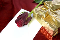 Gift wrapped in gold paper, red rose and a blank envelope Royalty Free Stock Photo