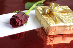 Gift Wrapped In Gold Paper, Red Rose And A Blank Envelope Stock Photo