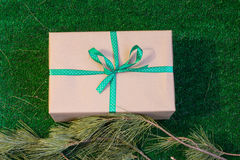 Gift wrapped in Kraft paper on a green background with branches of cedar. Stock Photo