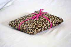 Gift wrapped in leopard print with pink ribbon Royalty Free Stock Photos