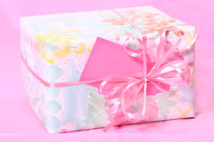 Gift Wrapped Package on pink Stock Photo