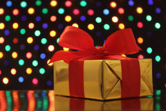 Gift wrapped present with a bow in front of a festive garland lights background Royalty Free Stock Image