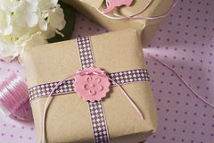 Gift wrapped in recyclable paper, ribbons and flower Royalty Free Stock Photography