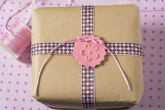 Gift wrapped in recyclable paper, ribbons and label flower Royalty Free Stock Photography
