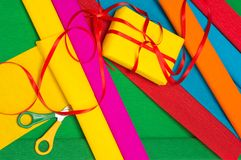 Gift wrapping. Wrapping paper, scissors and gift box with ribbon royalty free stock image
