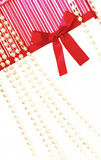 Gift wrapping . Gift wrapping with a red ribbon and pearls royalty free stock photo