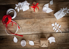 Gift wrapping. Gifts and paper flowers on a wooden background Stock Images