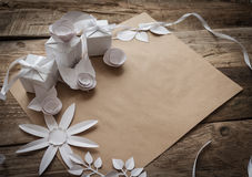Gift wrapping. Gifts and paper flowers on a wooden background Stock Photo