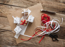 Gift wrapping. Gifts, pencil, scissors and tape on a wooden background Stock Images