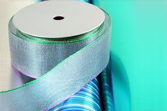 Gift Wrapping Materials. Spools of ribbon on rolls of gift wrap royalty free stock images