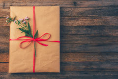 Gift in wrapping paper tied with red ribbon and daisy flower on wooden retro grunge background with space for text, top view close Stock Photos