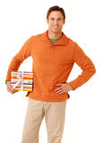 Gift for you. Portrait of a mature adult man wearing an orange sweater and khakis holding a gift isolated on white isolated on white stock photos
