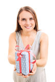 A gift for you. Beautiful young woman holding a gift, making an impression she's giving it to someone, isolated on white background Stock Image