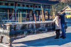Gifta paret nära rökelsekar ställde in brand pinnarna eller stearinljusen för jossaromrökelse i denYang templet i koreanen royaltyfri fotografi