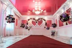 Gifta sig bågen i formen av två hjärtor i en korridor för ceremonier arkivbild