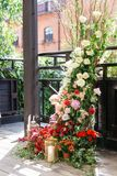 Gifta sig bågen med mycket nya blommor och stearinljus på golv Blomma garneringen Royaltyfri Foto
