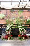 Gifta sig bågen med mycket nya blommor och stearinljus på golv Blomma garneringen Arkivbilder