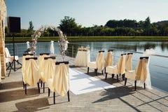 Gifta sig bågen med stolar och många blommor och dekor Arkivbild