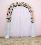 Gifta sig bågen som stället av konstgjorda blommor som dekoreras med tyg Arkivfoto