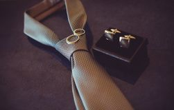 Gifta sig bandet, guld- vigselringar och cufflinks, mörk hemtrevlig färg Fotografering för Bildbyråer