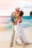 Gifta sig. Bbride och brudgum som kysser på den tropiska kusten på sunse Arkivbilder
