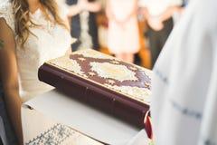 Gifta sig bidar par, och brudgummen får gift i en kyrka Royaltyfria Bilder