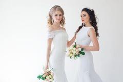 Gifta sig brud två med en bukett av blommor som gifta sig hår Fotografering för Bildbyråer
