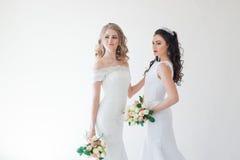 Gifta sig brud två med en bukett av blommor som gifta sig hår Arkivbild