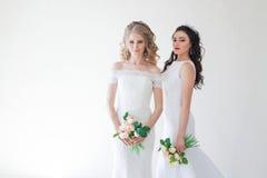 Gifta sig brud två med en bukett av blommor som gifta sig hår Royaltyfri Fotografi