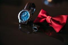 Gifta sig brudgumtillbehör, detaljer av kläder, fluga, manschettknappar, guld- cirklar Fotografering för Bildbyråer