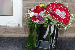 Gifta sig bukett två av röda rosor och annan färgrik blommor och mobiltelefon Royaltyfri Bild