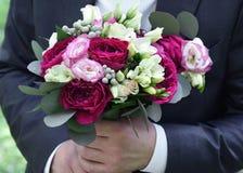 Gifta sig buketten i händer på brudgummen täta blommor upp arkivbild
