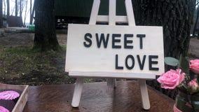 Gifta sig dekorativt område med drinkar med lemonad, muffin och ett tecken med den söta förälskelsen för uttryck arkivfilmer
