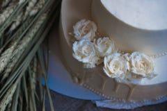 Gifta sig den kräm- kakan på lantlig bakgrund Härligt gourmet- syrligt som dekoreras med vita rosor och öron av vete arkivfoto