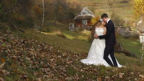 Gifta sig det hellånga skottet av den unga attraktiva nygifta personen koppla ihop förälskat krama ömt i byn i höst stock video