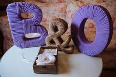 Gifta sig guld- cirklar i en träask på den vita bakgrunden Blått tecken av tyg Fotografering för Bildbyråer
