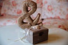 Gifta sig guld- cirklar i en träask på den vita bakgrunden Brunt tecken av tyg Royaltyfria Bilder