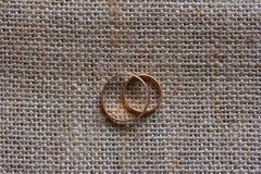 Gifta sig guld- cirklar på bakgrunden av mats Royaltyfri Bild