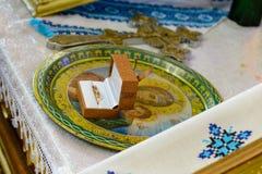 Gifta sig guld- cirklar som står på en platta i kyrkan arkivfoton