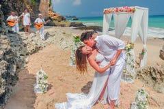 Gifta sig härliga par att gifta sig precis och kyssa på stranden Royaltyfri Fotografi