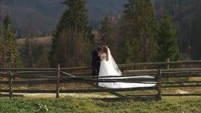 Gifta sig i berg Den attraktiva brudgummen är hållande och kyssa händer av hans underbara brud under gå i by lager videofilmer