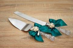 Gifta sig kniv- och kakaskyffeln dekorerade på trätabellen Royaltyfri Fotografi