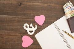 Gifta sig kostnadsbegrepp Hjärtor penna, papper, pengar på Wood Backgro Royaltyfri Fotografi