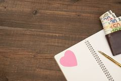 Gifta sig kostnadsbegrepp Hjärtor penna, papper, pengar på Wood Backgro Royaltyfri Bild