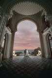 Gifta sig kyssen under bågen av slotten Fotografering för Bildbyråer