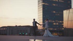 Gifta sig nyligen att älska par går nära en skyskrapa stock video
