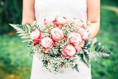Gifta sig nyligen kvinnan som rymmer hennes brud- bukett i en grön trädgård arkivfoto