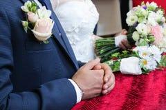Gifta sig oroar en man på ett bröllop, knäppte fast händer, ollon royaltyfri bild