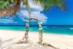 Gifta sig på stranden Gifta sig ärke- som dekoreras av vinrankor och flowe Arkivfoto