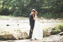 Gifta sig par, brudgummen och bruden som kramar, utomhus- near flod Arkivbild
